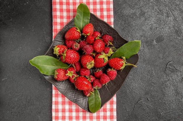 Draufsicht frische rote erdbeeren innerhalb platte auf dunkler tischfarbe beere himbeerfrucht