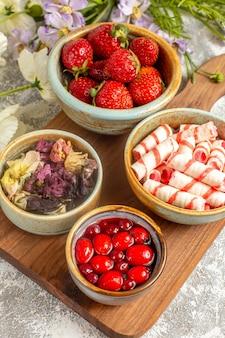 Draufsicht frische rote erdbeeren mit blumen auf weißer oberfläche beerenfrucht rote süßigkeit
