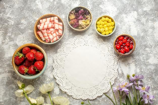 Draufsicht frische rote erdbeeren mit bonbons auf weißen oberflächenfarbe beerenfruchtbonbons