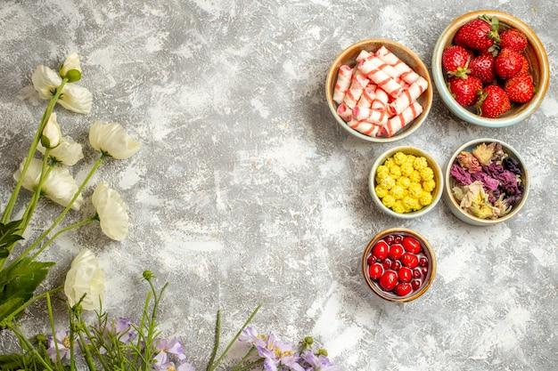 Draufsicht frische rote erdbeeren mit bonbons auf weißer oberfläche beerenbonbonfrucht