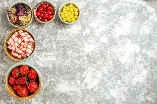 Draufsicht frische rote erdbeeren mit bonbons auf weißer oberfläche beerenfrucht rote bonbons