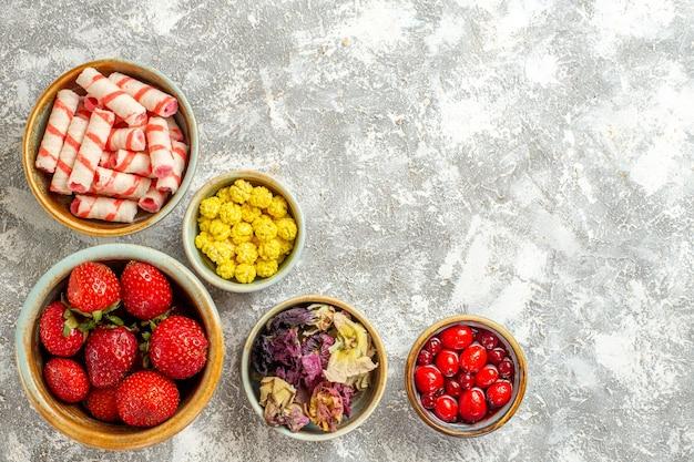Draufsicht frische rote erdbeeren mit bonbons auf weißer oberfläche früchte süße bonbonfarbe