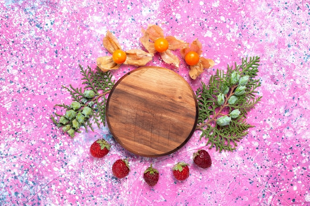 Draufsicht frische rote erdbeeren mit physalisiert auf rosa schreibtisch.
