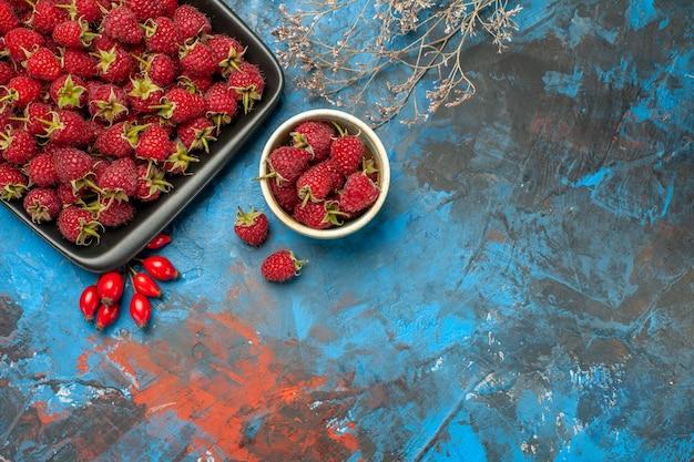 Draufsicht frische rote himbeeren im schwarzen tablett auf blauem hintergrund