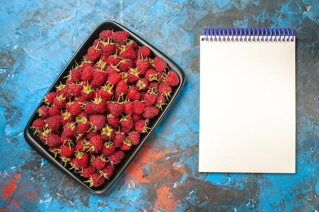 Draufsicht frische rote himbeeren im schwarzen tablett mit notizblock auf blauem hintergrund