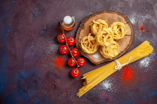 Draufsicht frische rote tomaten mit rohen nudeln auf dunklem schreibtisch rohen salat nudelessen mahlzeit