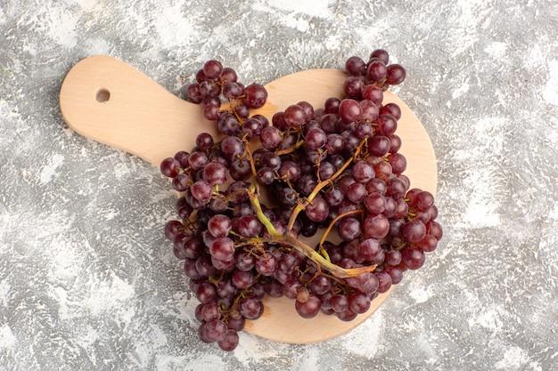 Draufsicht frische rote trauben milde und saftige früchte auf hellweißer oberfläche