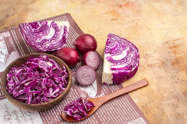 Draufsicht frische rote zwiebeln und eine schüssel mit gehacktem rotkohl für gemüsesalat auf holzhintergrund mit kopierplatz