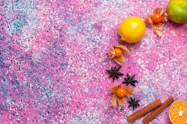 Draufsicht frische saure mandarinen mit zitronen und zimt auf dem hellrosa hintergrund.