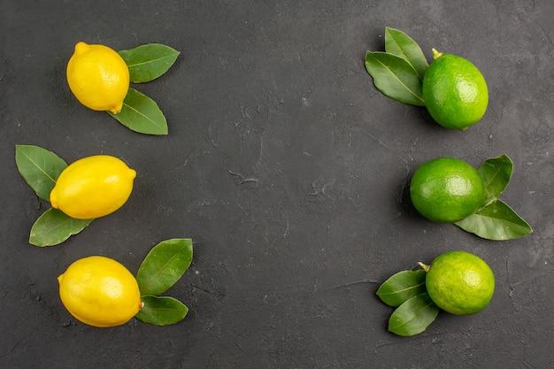 Draufsicht frische saure zitronen auf dem dunklen tisch limettenfrucht zitrusfrucht weich reif