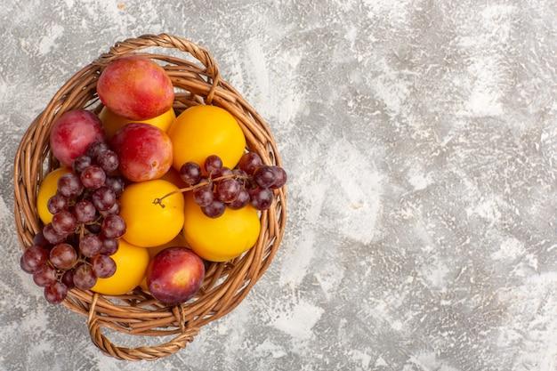 Draufsicht frische süße aprikosen mit pflaumen und trauben im korb auf weißem schreibtisch