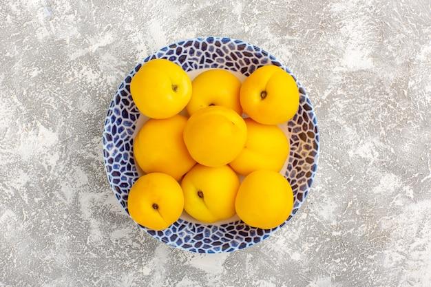 Draufsicht frische süße aprikosengelbe früchte innerhalb platte auf weißer oberfläche