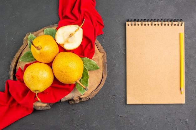 Draufsicht frische süße birnen auf rotem gewebe und dunklem tisch frisch reif mellow