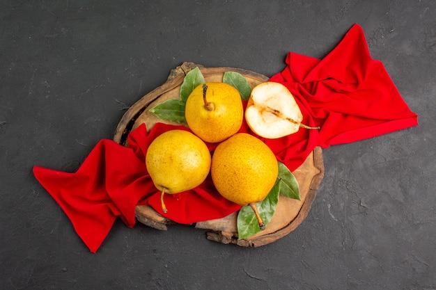 Draufsicht frische süße birnen auf rotem gewebe und dunklem tisch frische farbe reif weich
