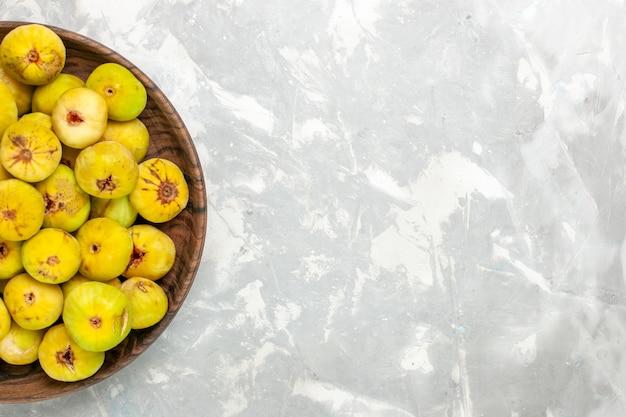 Draufsicht frische süße feigen in brauner platte auf dem hellen schreibtisch