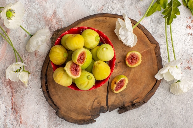Draufsicht frische süße feigen köstliche feten innerhalb der roten platte mit blumen auf weißem schreibtisch