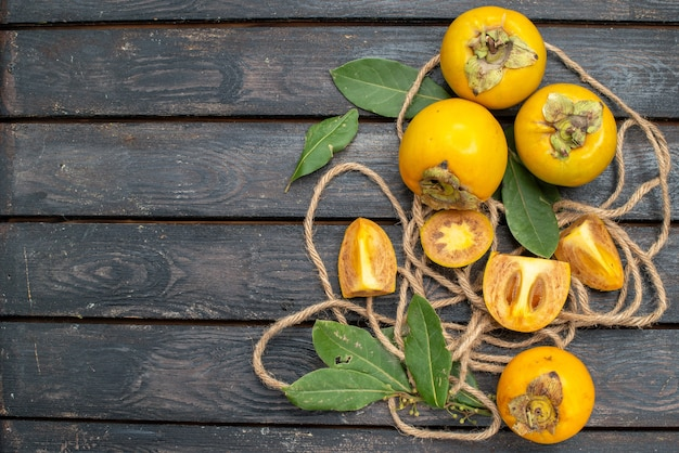 Draufsicht frische süße kakis auf rustikalem holztisch, früchte weich