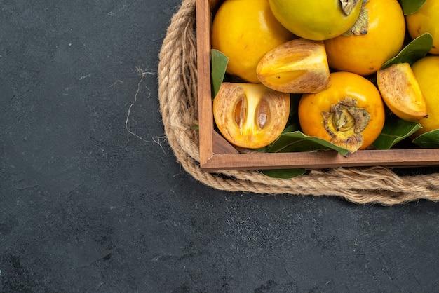 Draufsicht frische süße kakis innerhalb der schachtel auf dem dunklen tisch schmecken reife früchte