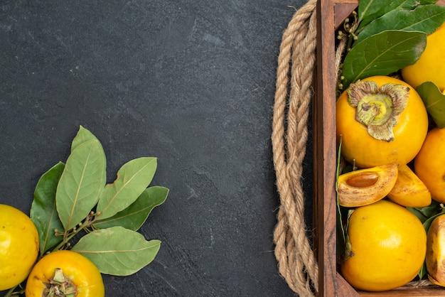 Draufsicht frische süße kakis innerhalb der schachtel auf dunklem boden reifen fruchtgeschmack