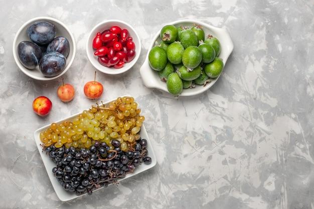 Draufsicht frische trauben mit feijoa und hartriegeln auf weißer oberfläche frucht milder vitaminsaft