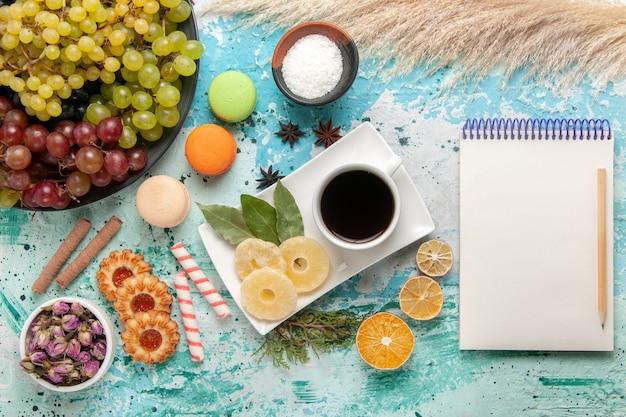 Draufsicht frische trauben mit französischen macarons keksen und tasse tee auf hellblauem schreibtisch kekse kekszucker süßer kuchentee