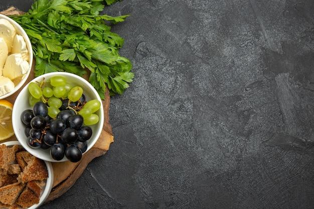 Draufsicht frische trauben mit käsegrün und zitronenscheiben auf dunkler oberfläche