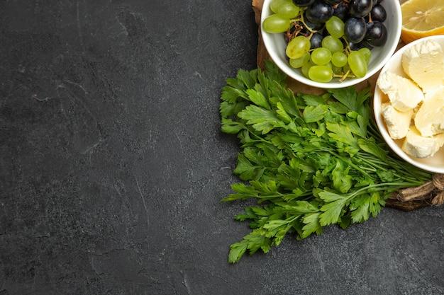 Draufsicht frische trauben mit weißem käsegrün und zitrone auf dunkler oberflächenmahlzeit fruchtmilchnahrung