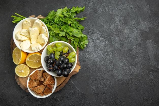 Draufsicht frische trauben mit weißem käsegrün und zitronenscheiben auf der dunklen oberfläche