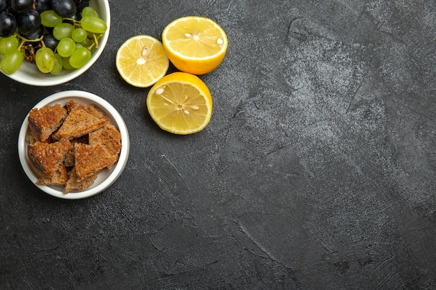 Draufsicht frische trauben mit zitronenscheiben auf dunkler oberfläche früchte reifes baumvitamin
