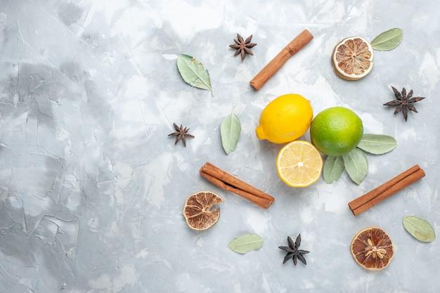 Draufsicht frische zitronen saftig und sauer mit zimt auf leichten schreibtisch tropischen exotischen fruchtzitrusfrüchten