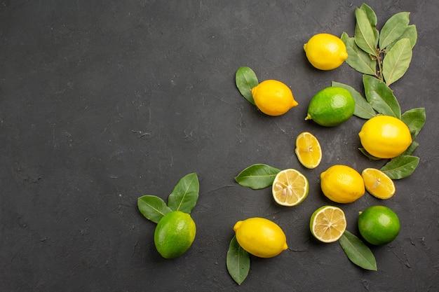 Draufsicht frische zitronen saure früchte auf dem dunklen tisch zitrus limettenfrucht