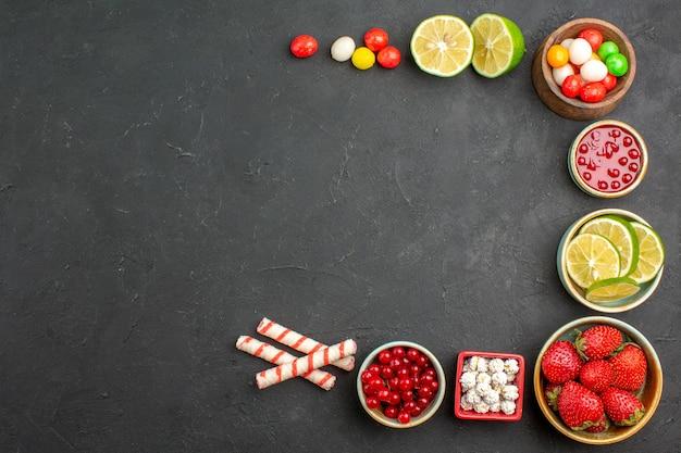 Draufsicht frische zitronenscheiben mit süßigkeiten und früchten