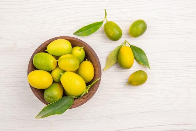 Draufsicht frische zitrusfrüchte im teller auf weißem hintergrund obst reife ernährung exotische farbe