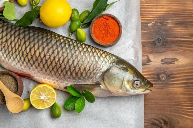Draufsicht frischer fisch mit zitronen auf einem braunen schreibtisch