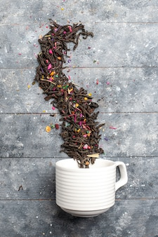 Draufsicht frischer getrockneter tee innen und außen tasse auf dem grauen rustikalen schreibtisch