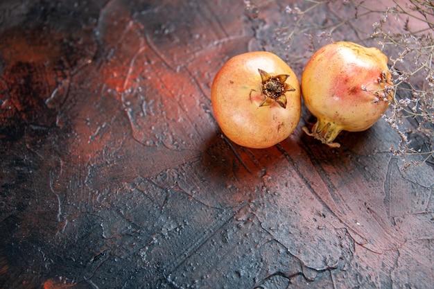 Draufsicht frischer granatäpfel getrockneter wildblumenzweig auf dunkelrotem hintergrund