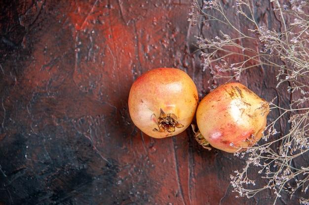 Draufsicht frischer granatäpfel getrockneter wildblumenzweig auf dunkelrotem holzhintergrund