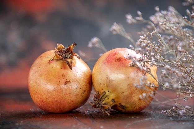 Draufsicht frischer granatäpfel getrockneter wildblumenzweig auf dunkelrotem isoliertem hintergrund