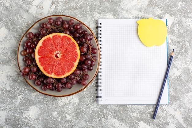 Draufsicht frischer grapefruitring mit rotem traubennotizblock auf der weißen oberfläche