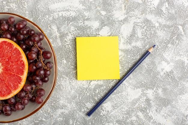 Draufsicht frischer grapefruitring mit roten trauben und aufkleber auf der weißen oberfläche