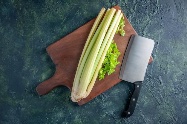 Draufsicht frischer grüner sellerie mit großem messer auf dunkelblauem hintergrundsalatgesundheitsdiätlebensmittelmahlzeit-farbfoto
