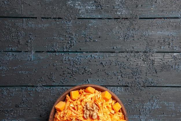 Draufsicht frischer karottensalat geriebener salat mit walnüssen und knoblauch auf einem dunklen schreibtisch diät reife farbe salat gesundheit