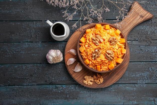 Draufsicht frischer karottensalat mit knoblauch und walnüssen auf dunkelblauem schreibtisch nuss-diät-gesundheitssalat gemüsefarbe