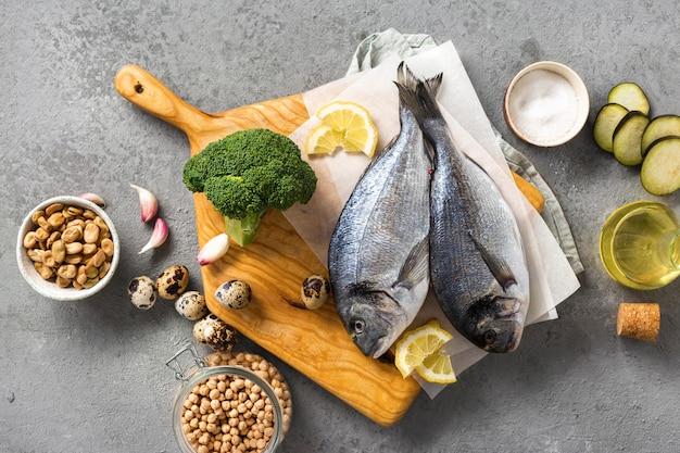 Draufsicht frischer lebensmittelhintergrund rohe kochzutaten für leckeres und gesundes essen. frischer fisch, gemüse und hülsenfrüchte