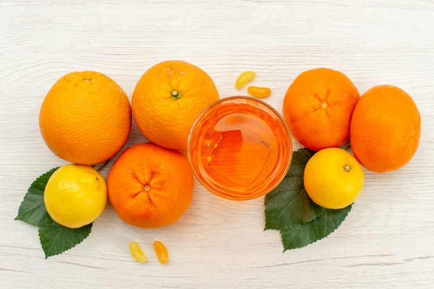 Draufsicht frischer orangensaft mit orangen und zitrusfrüchten auf exotischem tropischem fruchtsaft mit weißer oberfläche