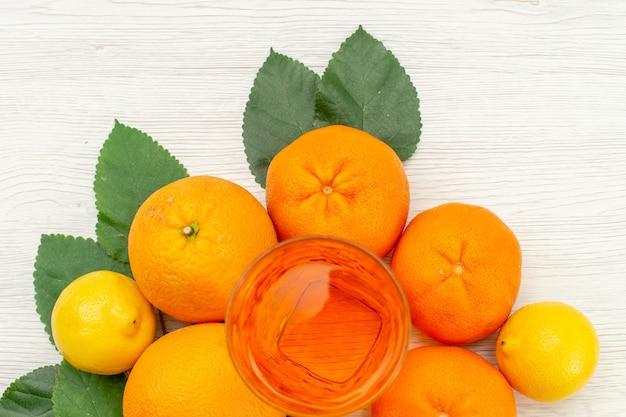 Draufsicht frischer orangensaft mit orangen und zitrusfrüchten auf hellweißer oberfläche zitrus exotischer tropischer fruchtsaft