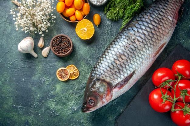 Draufsicht frischer roher fisch mit tomaten und grüns auf dunklem hintergrund