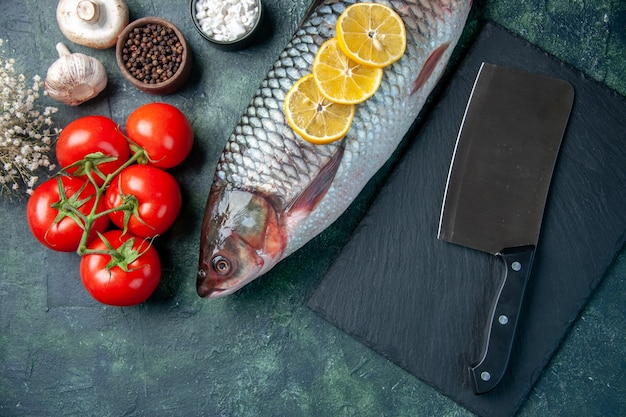 Draufsicht frischer roher fisch mit zitronenscheiben und tomaten auf dunkelblauem hintergrund