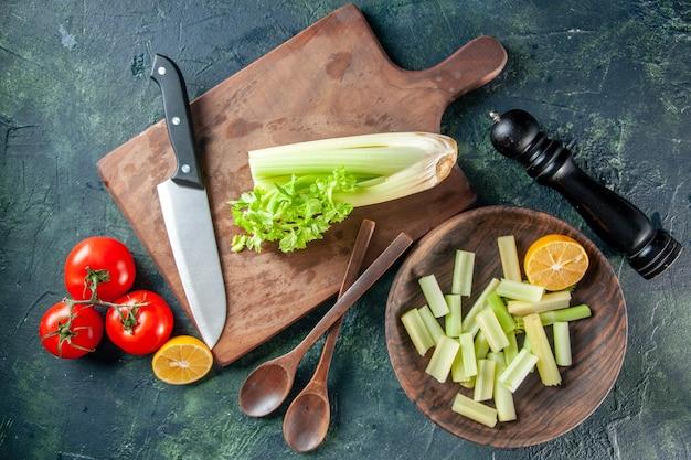 Draufsicht frischer sellerie mit roten tomaten auf dunklem tischsalat-diätmahlzeitfoto-nahrungsmittelgesundheitsfarben, die küche kochen