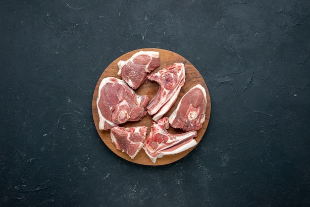 Draufsicht frisches fleisch schneidet rohes fleisch auf rundem holztisch auf dunkler lebensmittelfrische tierkuhmehlküche